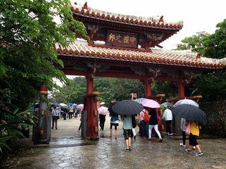 傘を差して首里城・守礼門を歩く観光客=20日午前、那覇市