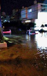 タクシーの窓まで冠水した道路=17日夜、糸満市潮平(読者提供)