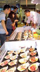 焼肉を提供する店で、陳列ケースに並ぶ肉を品定めする観光客ら=那覇市牧志の琉球王国市場