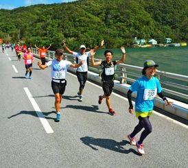 豊かな自然の中を走るランナー=西表島、浦内橋