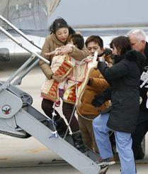 母親に抱きかかえられ、医療用小型ジェットに乗り込む翁長希羽ちゃん。中央は父親の司さん=19日午前、関西空港