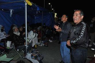 ゲート前に張ったテントで、歌を歌いながら新基地建設阻止へ気勢をあげる反対住民ら=11日午後9時39分、名護市辺野古