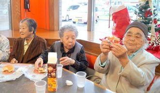 うれしそうにハンバーガーを頬張る「ハンバーグランチ会」の参加者=A&W名護店