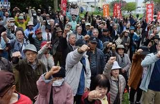沖縄平和運動センター議長の山城博治氏の釈放を訴え、拳を突き上げる市民たち=17日午前、那覇市楚辺の城岳公園