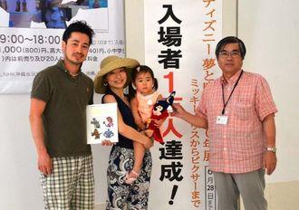 上原文化事業局長(右)から入場者1万人目の記念品が贈られた家村慶一郎さんと円さん、にこりちゃんの家族=19日、県立博物館・美術館