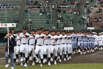 開会式で入場行進する各校の選手たち=21日、北谷公園球場