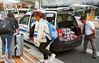 ワゴン型タクシーを利用する外国人観光客ら=6月1日、那覇市