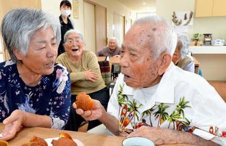 面会に訪れた娘のヨシ子さん(左)と話をしながらサーターアンダギーを頬張る110歳の津波蒲戸さん=読谷村・紅華の森