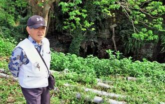 米軍の空襲に遭い、崖下にあった壕の入り口めがけて飛び込んだ当時を振り返る徳浜さん。「けがしなかったのが奇跡と思う高さだ」=八重瀬町具志頭
