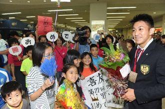 道場関係者に世界一を祝福される喜友名諒(右)=那覇空港