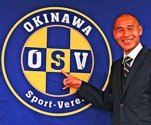 チームのロゴを指さし、笑顔を浮かべる高原直泰選手兼監督=那覇第2地方合同庁舎