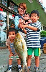 潮崎海岸で64センチのタマンを釣った玉城温志さん。父の釣果を披露する家族=15日