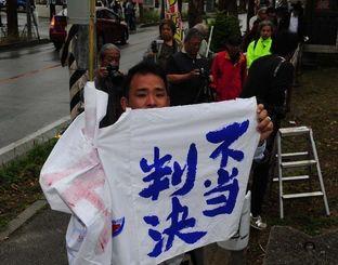 「不当判決」の旗を持つ原告団=24日午後1時27分、那覇市樋川