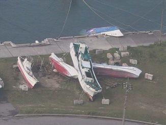 台風21号の影響で陸揚げされた漁船が横倒しに。船体が半分沈んだ船も確認された=29日午前8時57分、与那国町・久部良漁港(石垣海上保安部提供)