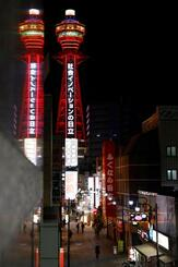 人がまばらな大阪・新世界と、赤く点灯した通天閣=4日夜