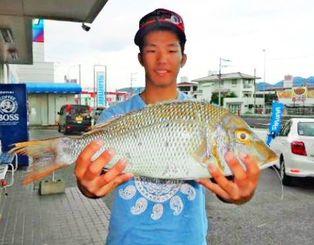 今帰仁海岸で53センチ、2キロのタマンを釣った金折貴洋さん=11月1日