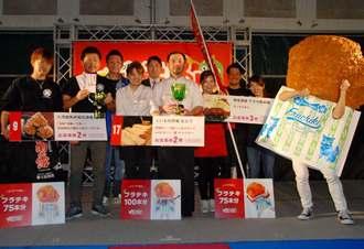 グランプリに選ばれた「くいもの市場むとう」の浜川義彦代表(前列左から4人目)と受賞者ら=11日、那覇市・奥武山公園