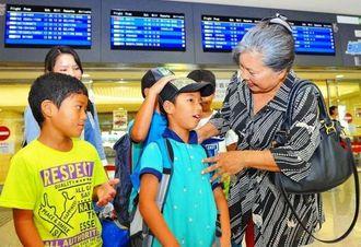 旧盆で帰省した親類との再会に笑顔があふれた=25日午後、那覇空港