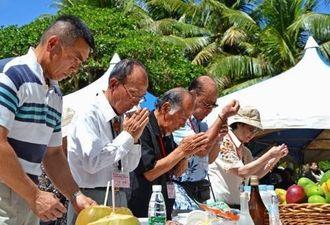 戦没者の冥福を祈り、手を合わせる遺族ら=25日、サイパン島