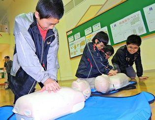 蘇生人形を使って心臓マッサージする小学生たち=宜野座村・宜野座小学校