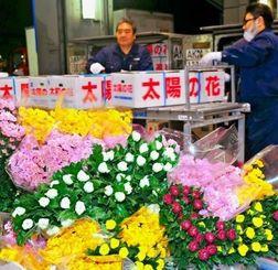 正月用の飾り花として、県外に出荷される県産菊などを積み込む作業員=2013年12月17日、那覇空港貨物ターミナルビル