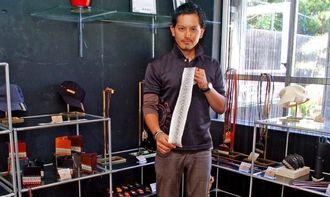 ハブを使って加工から商品化まで一貫して手掛けるyu-i FACTORYの幸地賢尚代表=南風原町新川の同社店舗