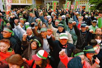 ガンバロー三唱で拳を突き上げる渡具知武豊さんの支持者=3日午後5時30分、名護十字路