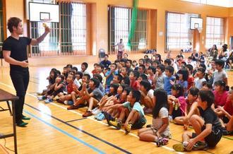 ペットボトルを使ってマジックを披露するMASAさん(左端)=9日、竹富町立上原小学校