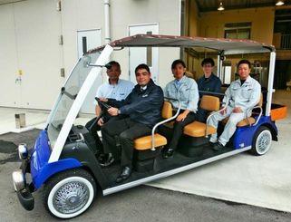 市販の電動カートを8人乗りに改造し、観光施設などへの導入を目指してハンドルを握る沖縄ヤマハの許田社長、mdnの松田さん(中央)ら=うるま市、mdnの研究施設