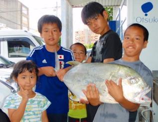 那覇港で88・5センチ、8・69キロのロウニンアジを釣った村吉海斗さん(右から2人目)=6月25日