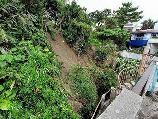民家裏手の擁壁上部で起きた土砂崩れ=18日午前10時半ごろ、那覇市首里石嶺町