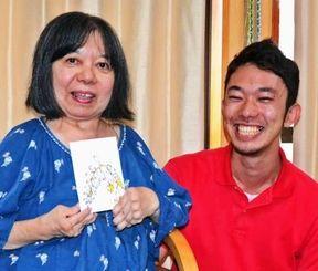 絵手紙を描きため、展示会を開いている宮城智子さん(左)とデイサービスで見守る比嘉浩司さん=沖縄市・いきがいのまちデイサービス