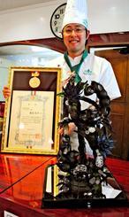 九州の洋菓子技術コンテストの部門別最優秀賞に選ばれた屋宜丈斗さん。手前が全てチョコでできた受賞作「スコーピオン」の試作品=9日午後、中城村北上原・「プチ・スウィート」