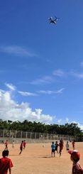 普天間第二小校庭の真上をオスプレイが飛び交う。敷地は米軍普天間飛行場とフェンス1枚で隔てられている=2013年8月3日、宜野湾市