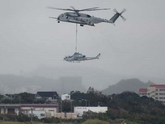 入砂島からCH53でつり下げられ、読谷村の米軍トリイステーションに移送される米軍普天間飛行場所属のAH1攻撃ヘリ=11日午前9時50分ごろ(読者提供)