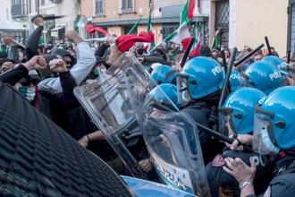 新型コロナに関わる政府の規制に反対するデモ隊と、警察の鎮圧部隊の衝突=31日、ローマ(AP=共同)