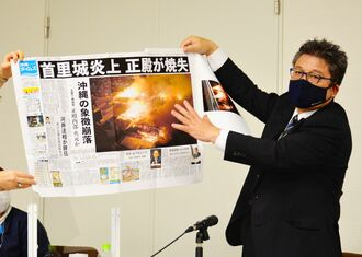 紙面を紹介しながら講演する沖縄タイムスの崎浜秀也写真部長=12日、横浜市中区のニュースパーク