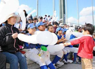 風船を膨らませて、ロッテの終盤攻撃に声援を送る少年野球の子どもたち=石垣市中央運動公園野球場