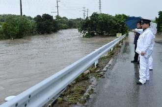 大雨で水かさが増した饒波川を警戒する警官ら=19日午後2時43分、八重瀬町宜次