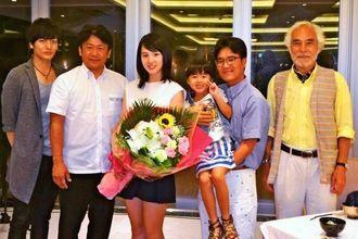 歓迎の花束を手にする桜庭さん(中央)やハン監督(右から2人目)=石垣市宮良、石垣リゾート