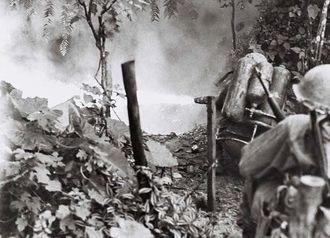 火炎放射器で洞穴の入り口の足場を焼き払う米兵=1945年6月7日、金武村