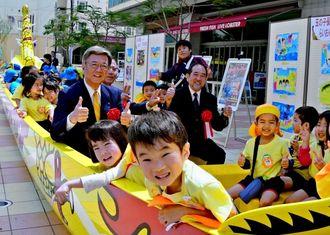 爬龍船のベンチに座って喜ぶ玉の子保育園の子どもたちと翁長雄志市長(中央左)ら=8日、那覇市安里のさいおんスクエア