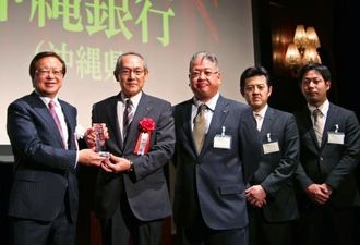 日本M&Aセンターの三宅社長(左)から表彰を受ける沖銀の伊計常務(左から2人目)と同行行員ら=5日、東京・シャングリ・ラホテル東京