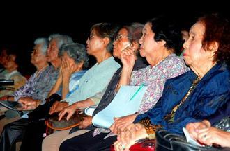 映画に見入る積徳高等女学校の元女学生ら。戦場の映像が流れると目を覆う人も=24日、県立博物館・美術館