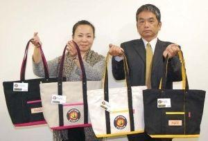 阪神タイガースモデルの帆布トートバッグをPRする宮城社長(左)、津輕氏=沖縄タイムス社