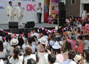 多くの参加者が見守る中、人前結婚式を挙げた入眞地順治さん(左)と安座間尚彦さん=17日、那覇市のテンブス館前広場