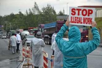 小雨が降る中、かっぱを着て抗議活動をする人々=8日午前9時すぎ、名護市辺野古の米軍キャンプ・シュワブゲート前