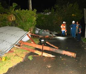 竜巻とみられる突風で飛ばされ、道路上に散乱するトタン屋根などを確認する消防署員ら=28日午後8時ごろ、名護市済井出