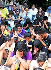 沖縄戦時、住民ら約560人の命を守った壕に、感謝の祈りをささげる潮平小6年の児童と潮平区民ら=2日、糸満市潮平の権現壕前