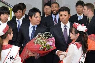 歓迎の花束を抱える緒方孝市監督(手前右)=那覇空港到着ロビー
